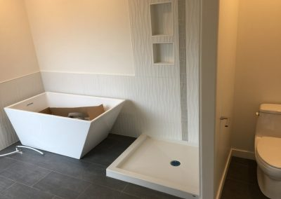 white bathroom with tub and toilet